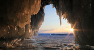 Winter Baikal. Ice cave with icicles at sunset. Winter Baikal. Ice cave with icicles at sunset stock footage