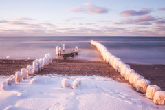Winter in the Baltic Sea , Poland. Winter seascape in the Baltic Sea , Poland, with a beautiful snow covered shore and frozen wooden pilings leading down into Royalty Free Stock Photo