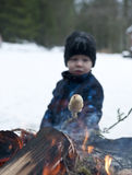 Winter barbecue. Young boy baking scones or bread on a stick over an open fire at wintertime Royalty Free Stock Photo