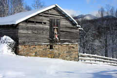 Winter Barn & Sled At Christmas. Winter scene with old wood & rock barn with sled on door and snowy mountains in the background Stock Photo
