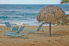 A winter beach of Atlantics. A natural palm umbrella and lying chairs on the beach os Sosua, Dominican Republic. Comfortable shelter from the blazing sun. Low Stock Images
