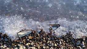 Frost water and pebbles royalty free stock photography