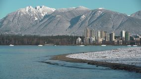 Winter Beach Snow, Kitsilano, Vancouver 4K UHD. Kitsilano Beach on English Bay in the early morning. In the background are the snowcapped North Shore Mountains stock video footage