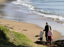 Winter Beach Walk. Family walking along the beach on cold winters day Stock Photos