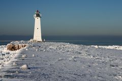 Winter Beacon. Bright sunlight on a beacon at the end of a snow-covered pier Stock Images