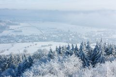 Winter beautiful landscape with trees covered with hoarfrost. A small European village is located among the snow-covered. Fields. Low clouds. Copypast royalty free stock photography