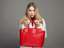 Winter beautiful Woman in Fur Coat. Beauty Fashion Model Girl. luxury stylish blond girl with red Handbag Royalty Free Stock Photos