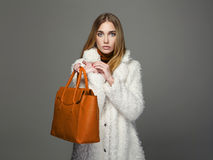 Winter beautiful Woman with orange Handbag. Beauty Fashion Girl in fur Stock Photos