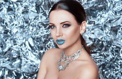 Winter beauty. Beautiful fashion model girl with blue snow lips. Holiday makeup on glitter shiny background and brilliant jewelry royalty free stock photos