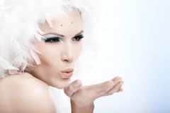 Winter beauty blowing a kiss in the air Royalty Free Stock Image
