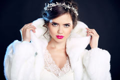 Winter beauty Elegant woman in white fur coat. Fashion model portrait isolated on dark background. Jewelry. Wedding hairstyle. Ma. Keup royalty free stock images