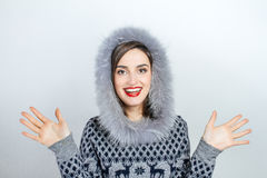 Winter beauty fashion. Beautiful face girl with trendy fur hat gesturing. Emotions. Professional makeup and manicure Stock Photos