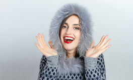 Winter beauty fashion. Beautiful face girl with trendy fur hat gesturing. Emotions. Professional makeup and manicure Royalty Free Stock Photo