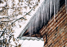 Winter beauty. The old brick house and icicles Stock Image