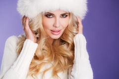 Winter beauty - portrait of a young woman. Studio portrait of a young woman - blonde with long curly hair and brown eyes, a white fluffy fur hat, a white scarf Stock Photo