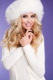 Winter beauty - portrait of a young woman. Studio portrait of a young woman - blonde with long curly hair and brown eyes, a white fluffy fur hat, a white scarf Royalty Free Stock Photo