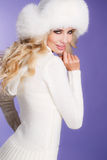 Winter beauty - portrait of a young woman. Studio portrait of a young woman - blonde with long curly hair and brown eyes, a white fluffy fur hat, a white scarf Royalty Free Stock Photography