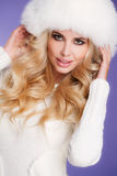 Winter beauty - portrait of a young woman. Studio portrait of a young woman - blonde with long curly hair and brown eyes, a white fluffy fur hat, a white scarf Royalty Free Stock Image