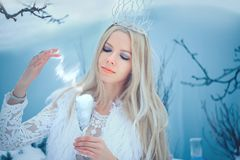 Winter Beauty Woman. Beautiful fashion model girl with glass flasks hairstyle and make-up in winter laboratory. Festive makeup and. Manicure. Winter Queen with royalty free stock photo