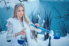 Winter Beauty Woman. Beautiful fashion model girl with glass flasks hairstyle and make-up in winter laboratory. Festive makeup and. Manicure. Winter Queen with royalty free stock photography