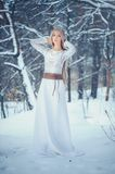 Winter Beauty Woman. Beautiful fashion model girl with snow hairstyle and makeup in the winter forest. Festive makeup and manicure. Winter Queen with snow and royalty free stock images