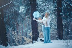 Winter Beauty Woman. Beautiful fashion model girl with snow hairstyle and makeup in the winter forest. Festive makeup and manicure. Winter Queen with snow and royalty free stock photography