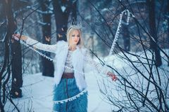 Winter Beauty Woman. Beautiful fashion model girl with snow hairstyle and makeup in the winter forest. Festive makeup and manicure. Winter Queen with snow and stock image