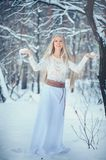 Winter Beauty Woman. Beautiful fashion model girl with snow hairstyle and makeup in the winter forest. Festive makeup and manicure. Winter Queen with snow and royalty free stock image