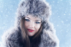 Winter beauty woman in a fur hat and mittens. Winter beauty woman in a fur hat and mittens over snowy background Royalty Free Stock Images