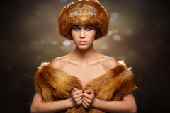Winter beauty young woman portrait. Portrait of a girl in a fur hat on a background of snowflakes Royalty Free Stock Image