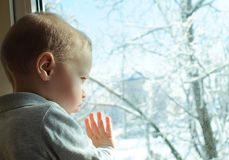 Winter behind a window. The child looks out of the window Royalty Free Stock Photos