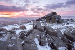 Winter on belstone tor Dartmoor. Winter sunrise on a snow covered belstone tor dartmoor devon uk stock photo