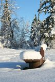 Winter bench. Snow covered park bench on a beautiful sunny day Stock Image