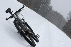 Winter bike. Bicycle on a winter road under falling snow Stock Images