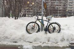Winter, the bike is in a snowdrift. At the pillar, the street in the snow. Front view royalty free stock photos