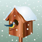 Winter bird house with little bird Royalty Free Stock Photo