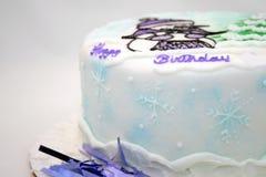 Winter birthday cake. White birthday cake with snowflakes, snowman and a tree Royalty Free Stock Photos