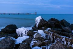 Winter Black Sea landscape from Burgas bay, Bulgaria. Blue hour sunset. Frozen rocks and bridge