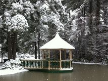Winter Bliss. Snow covered gazebo overlooking water  surrounded by snow covered pines Royalty Free Stock Photography