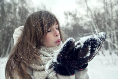 Winter blondy woman blowing snow on herself. Attractive winter woman play with snow Royalty Free Stock Photo