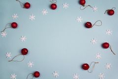 Winter blue background with red balls and snowflakes. Copy space Royalty Free Stock Images