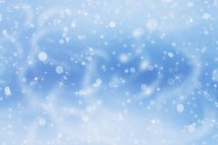 Winter blue landscape with falling white shining snow.... Stock Photos