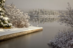 Winter Boat Dock. Landscape with the lake just starting to freeze and snow covered trees and island Royalty Free Stock Images
