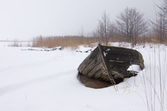 Winter boatwreckage. Broken wooden-boat at the beach.  (in the winter Stock Photos