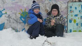 Winter bonfire smoke. Winter fire. Two small boys sit squatting and watch the smoke firecrack burn. A boy with glasses. On the street. Children are dangerously stock footage