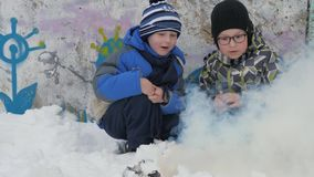 Winter bonfire smoke. Winter fire. Two small boys sit squatting and watch the smoke firecrack burn. A boy with glasses. On the street. Children are dangerously stock video