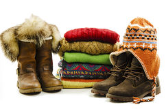Winter boots, cap and stack of various sweaters. Winter style Royalty Free Stock Photos