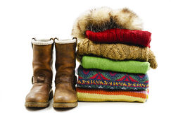 Winter boots, cap and stack of various sweaters. Winter style Royalty Free Stock Image