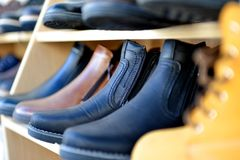 Winter boots display for sale in clothing store. Image of a Stock Photography