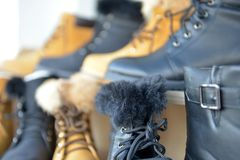 Winter boots display for sale in clothing store. Image of a Stock Photo